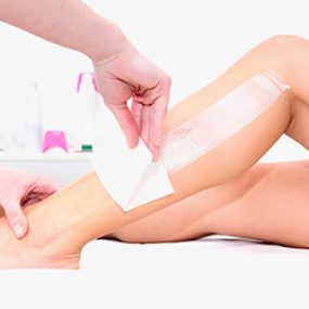 Waxing female's legs in beauty salon
